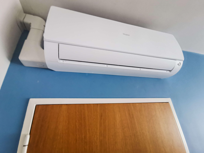Airco gepositioneerd boven een deur in een felblauwe kamer.