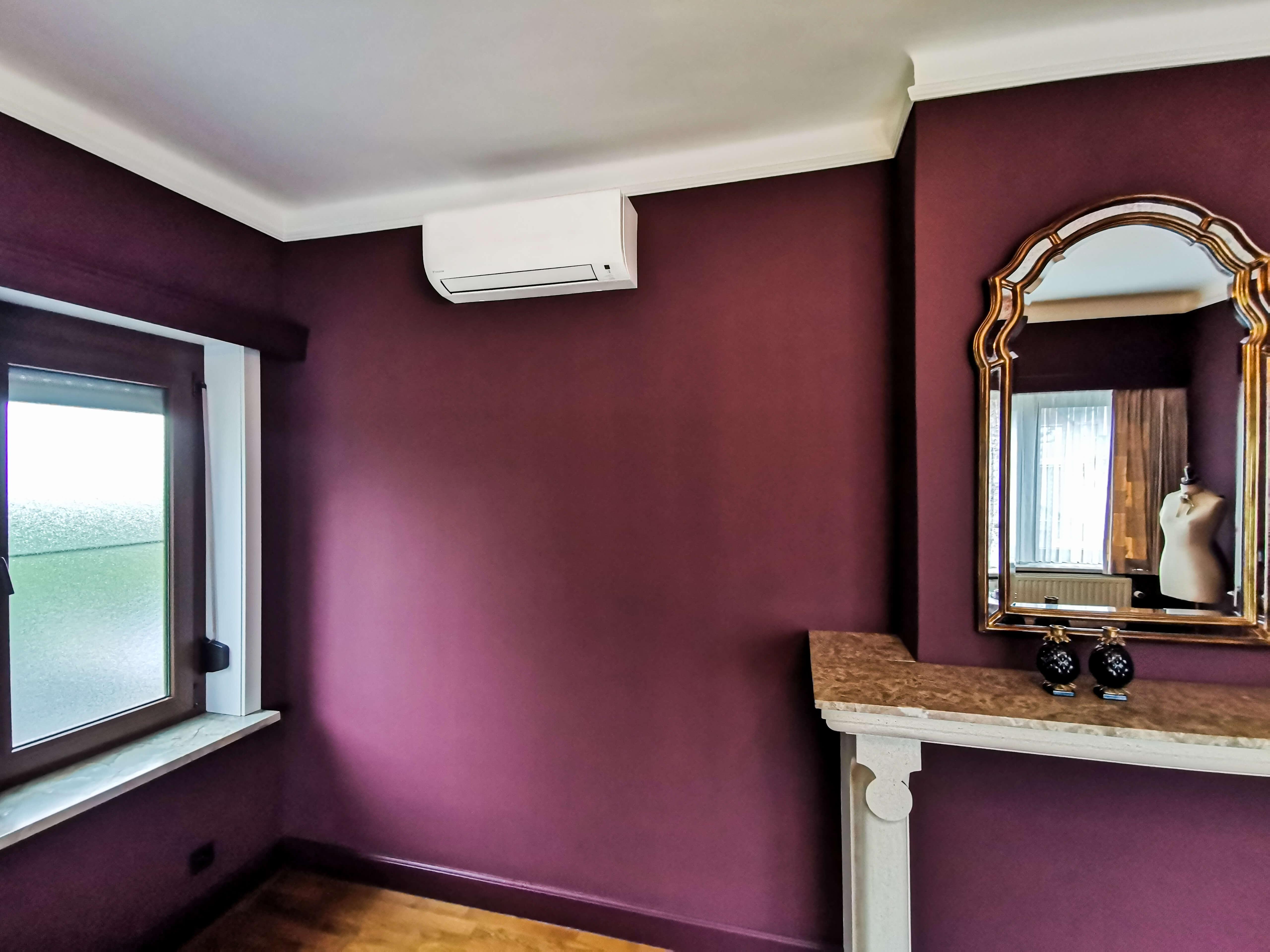 Airco koelt een ruime kamer met muren in het bordeaux
