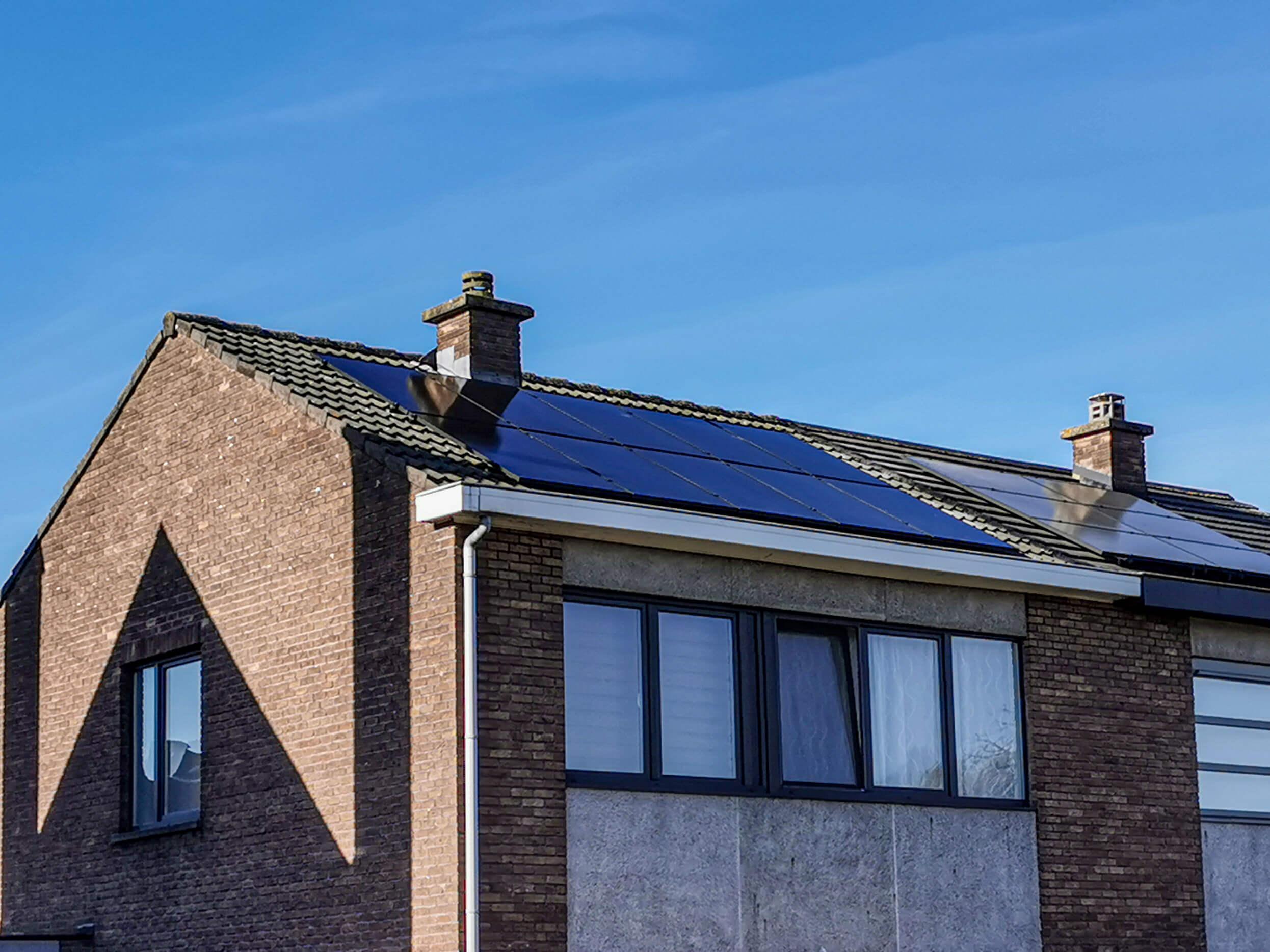 10 zonnepanelen op een dak bij helder blauwe hemel in het waasland