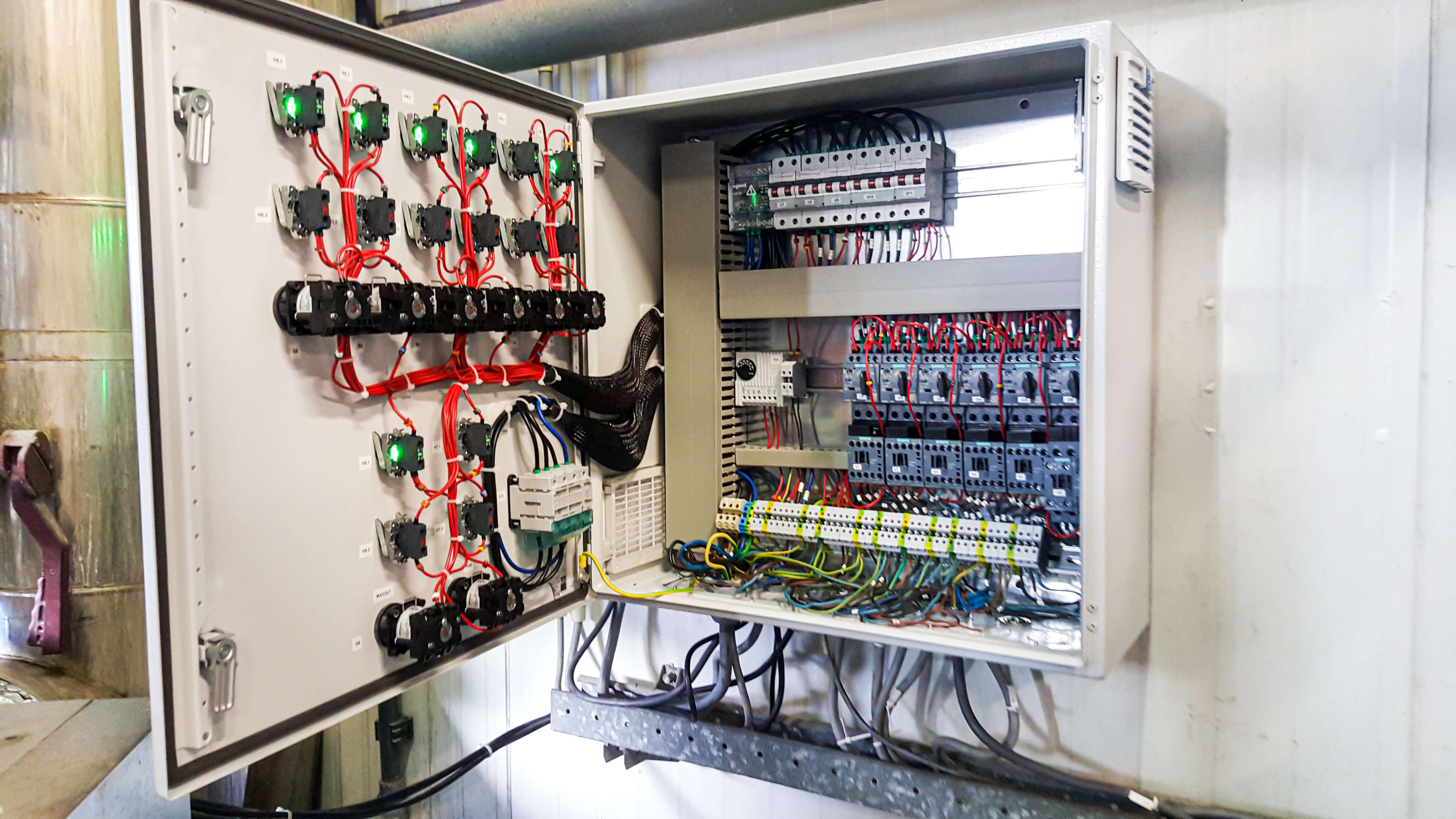 Heraanleggen van een witte sturingskast met allerlei gekleurde kabels.