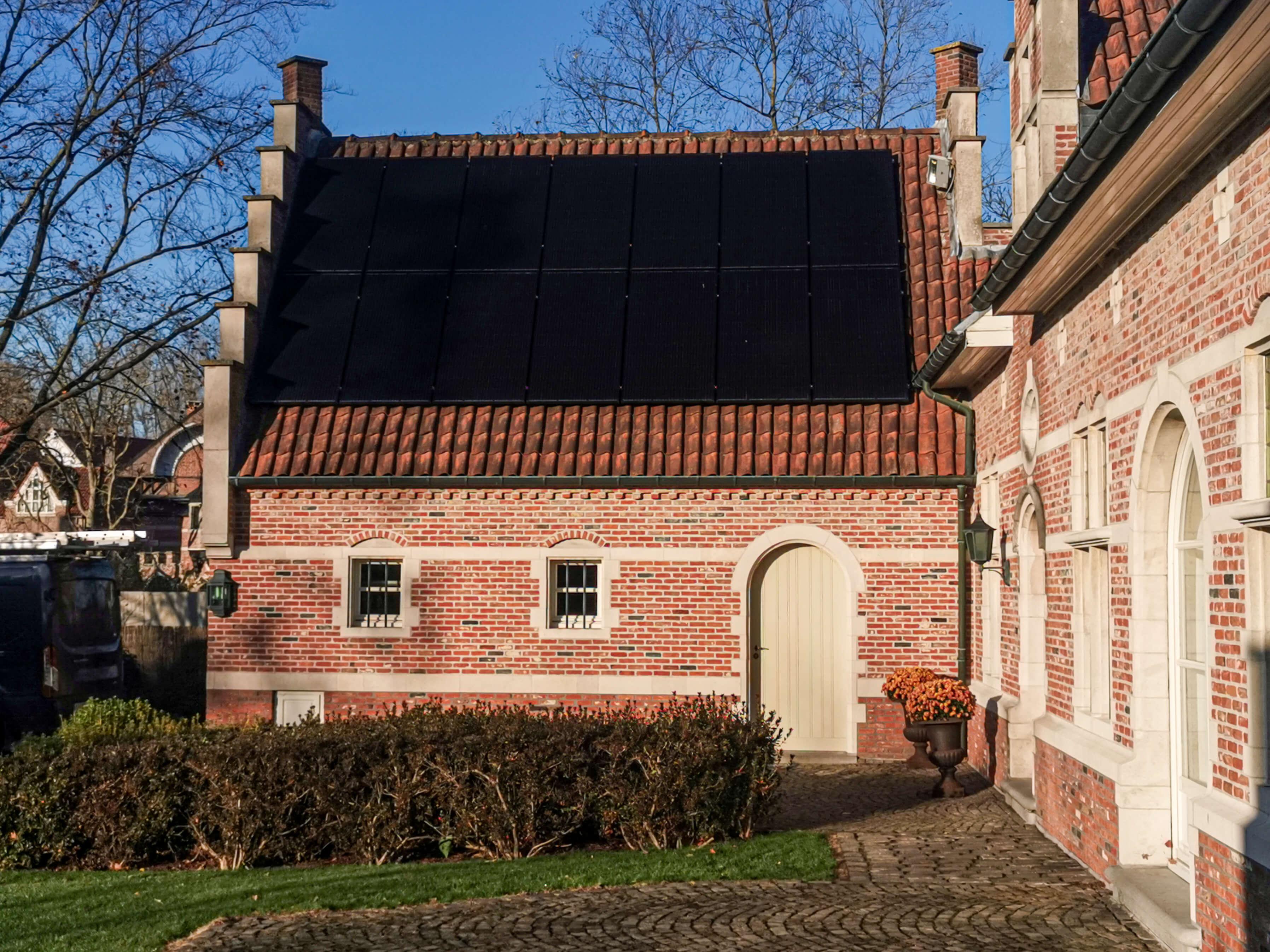 14 zonnepanelen op het dak van een bijgebouw in landelijke stijl.