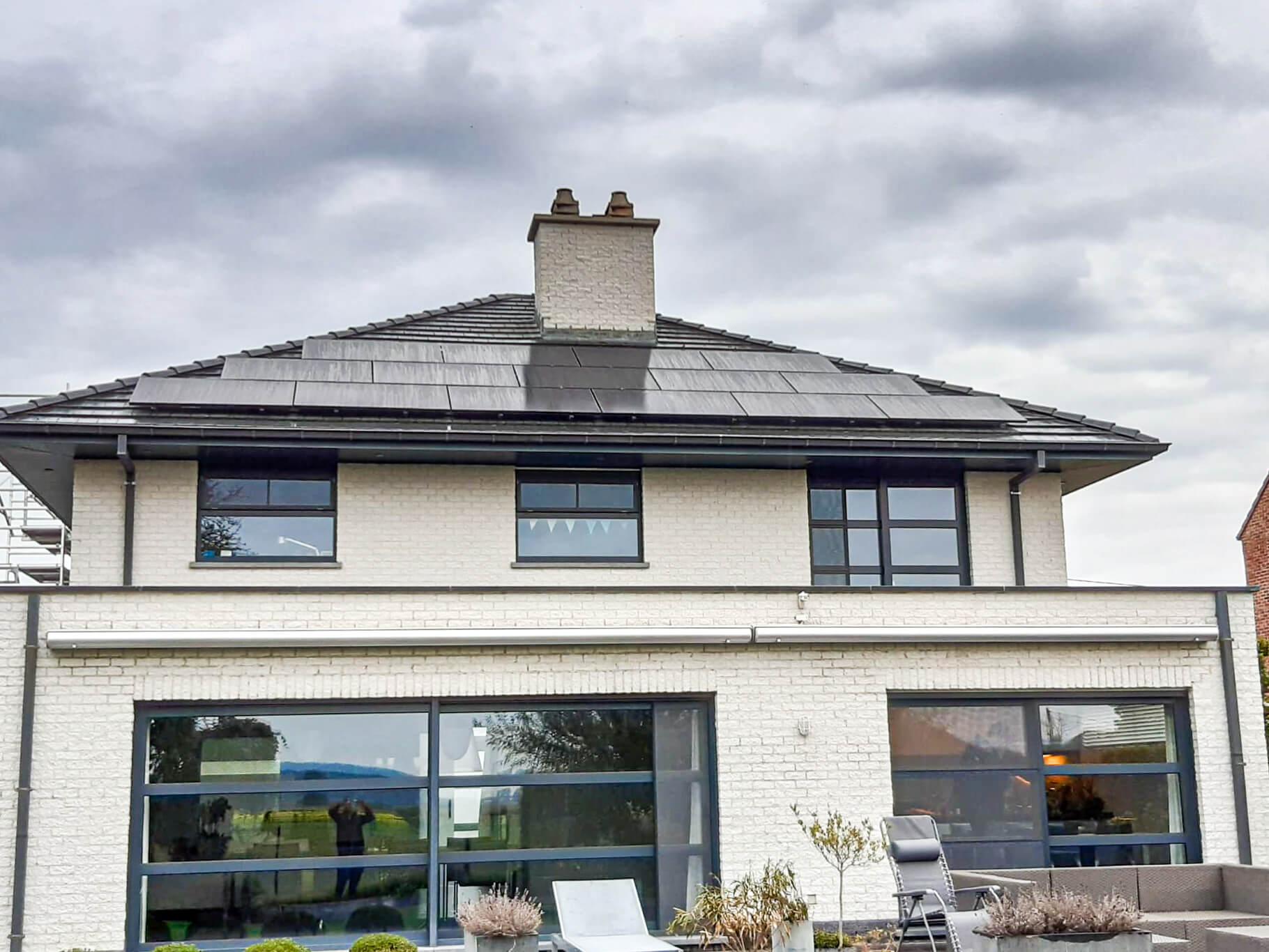 15 zonnepanelen op het dak van een grote woning met witte gevelsteen tegen een bewolkte hemel in het waasland.