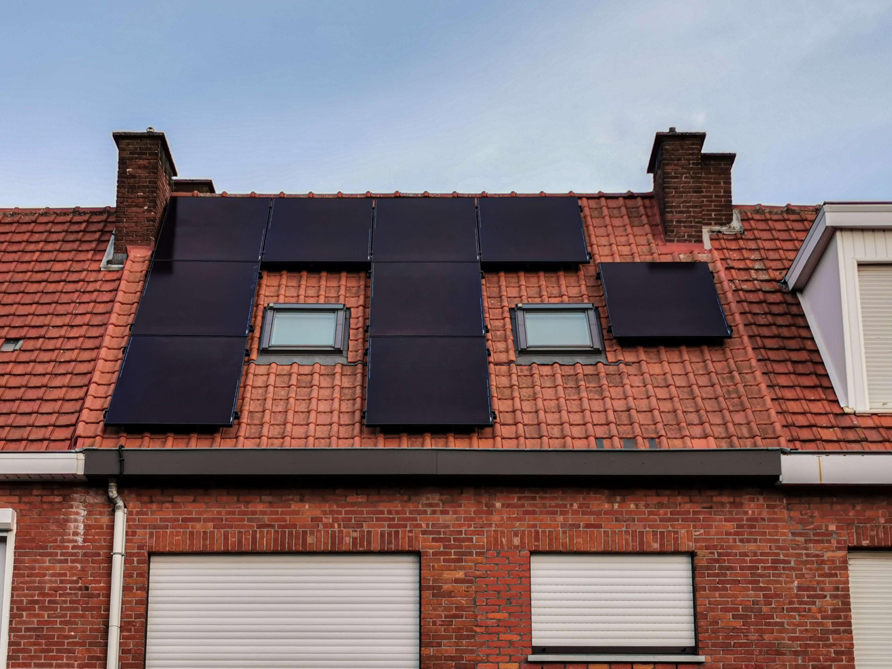 Frontaal aanzicht van een rijhuis met zonnepanelen op het dak.