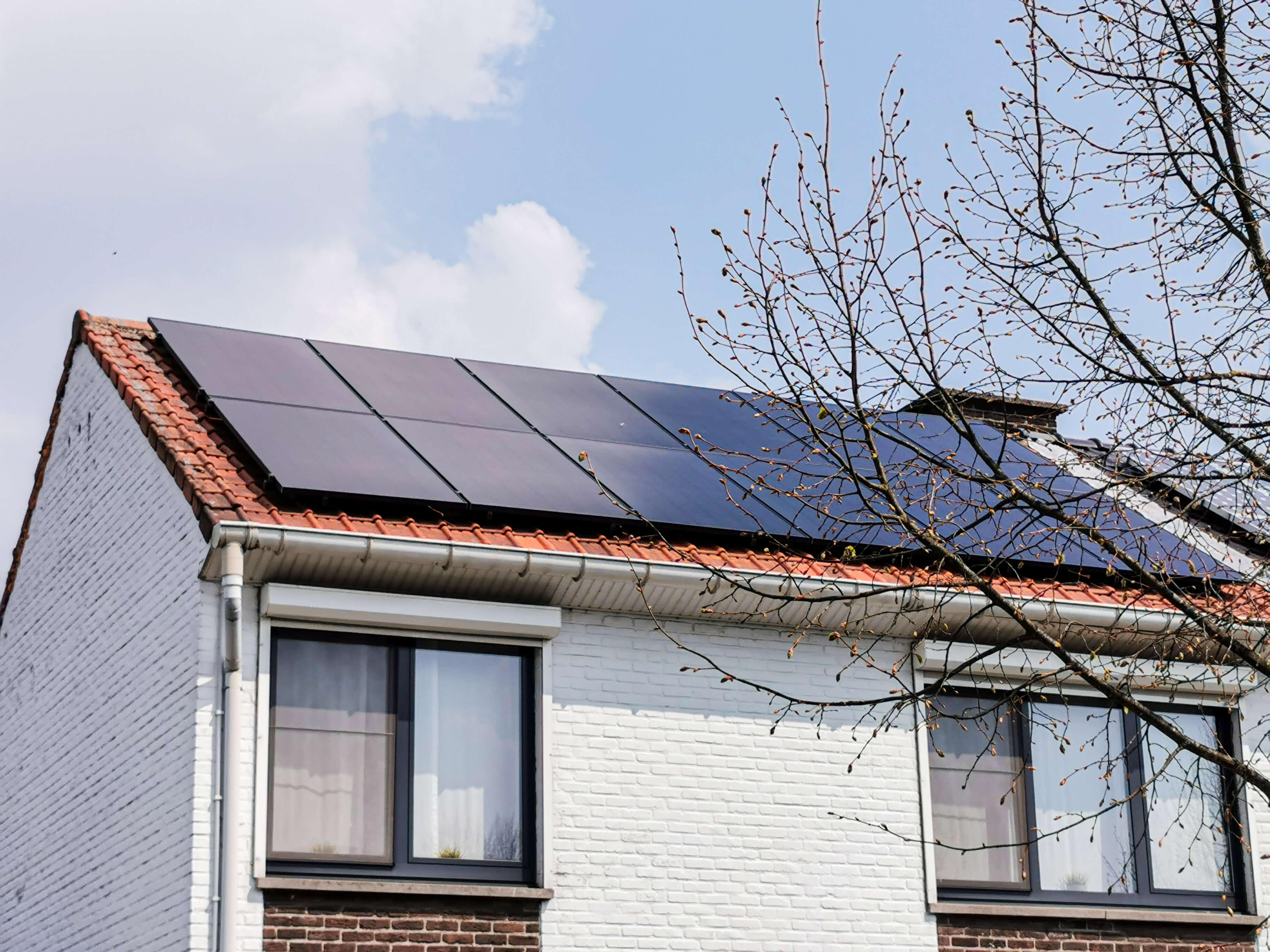 Zonnepanelen op het dak van een wit geverfde woning in het waasland.