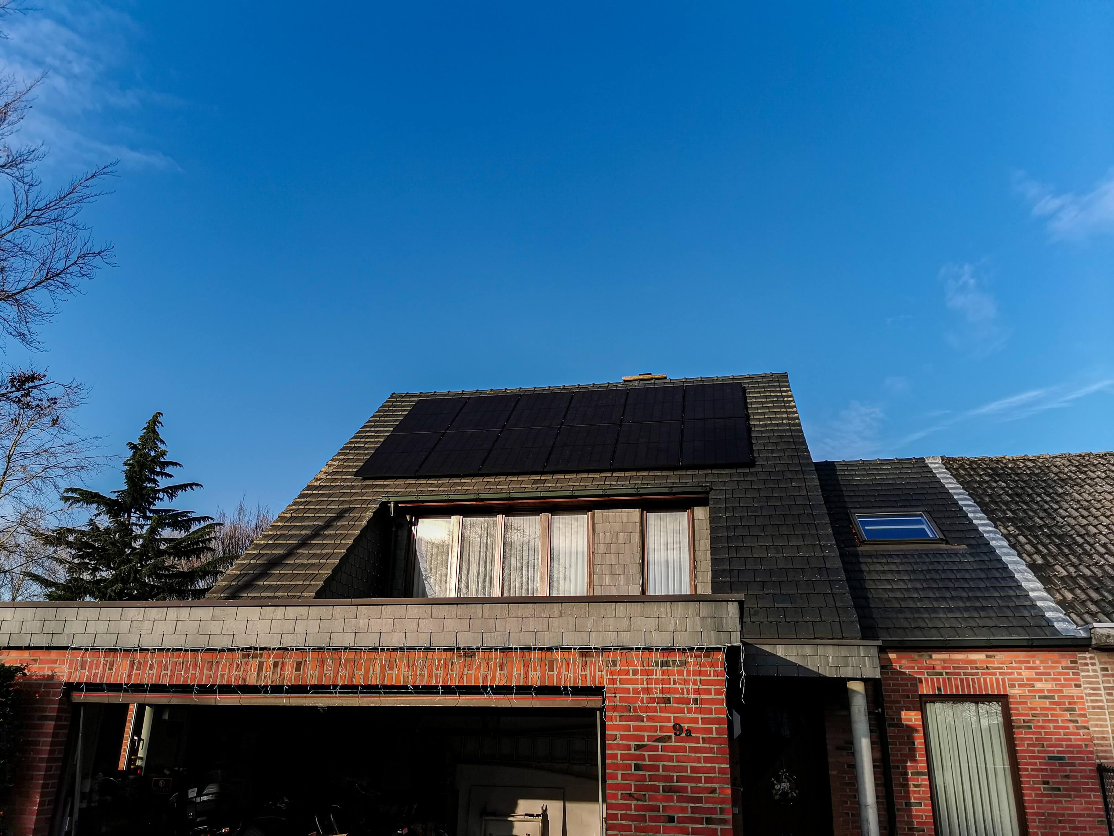 Frontaal aanzicht dak met zwarte zonnepanelen tegen helderblauwe hemel.