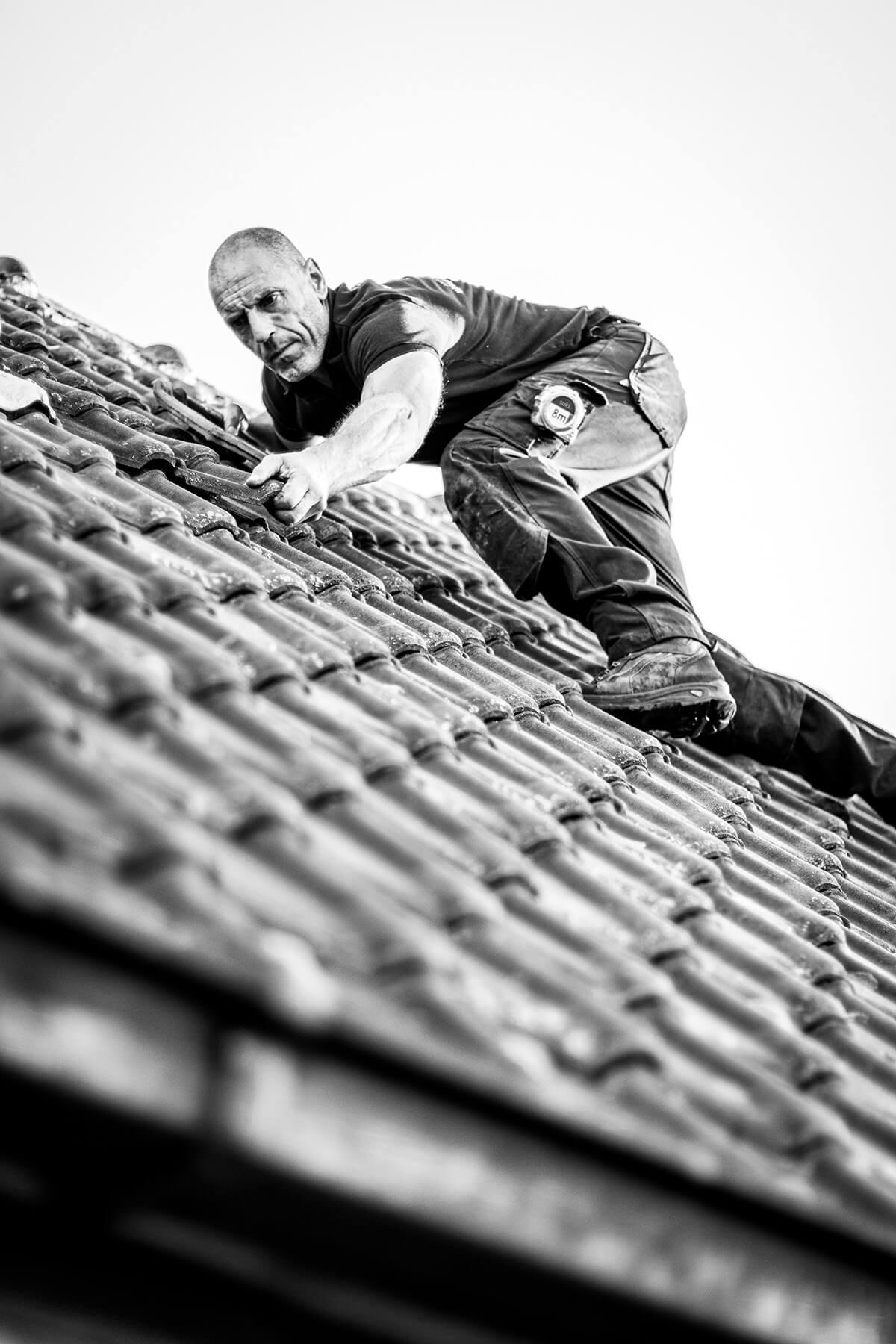 Zonnepanelen installateur verlegt dakpannen op een dak in het Waasland.