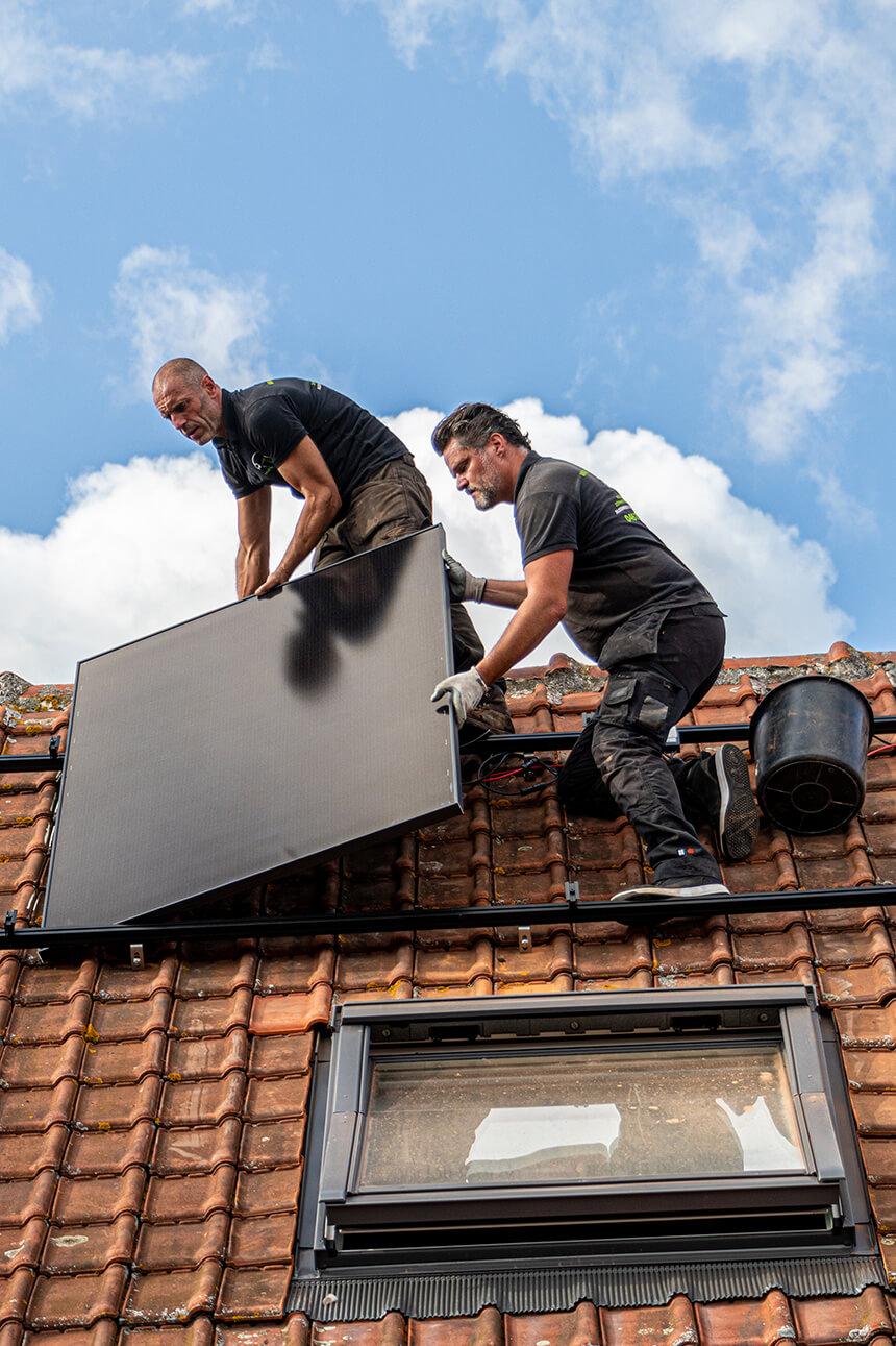 Twee zonnepanelen installateurs plaatsen samen een paneel op een dak in het waasland tegen helder blauwe hemel.