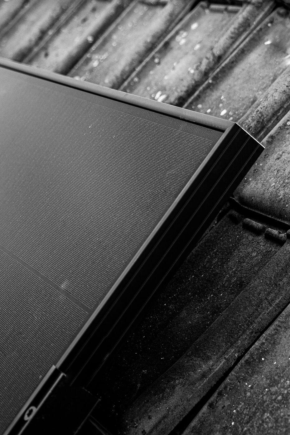 Detail van de rechterbovenhoek van een zonnepaneel in zwart-wit.