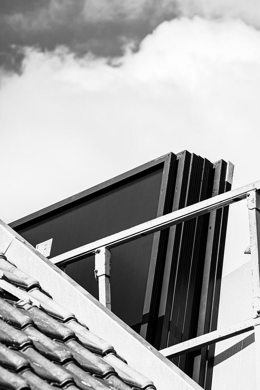 6 zonnepanelen achter elkaar op de hoogtewerker naast een dak. (Zwart-wit)