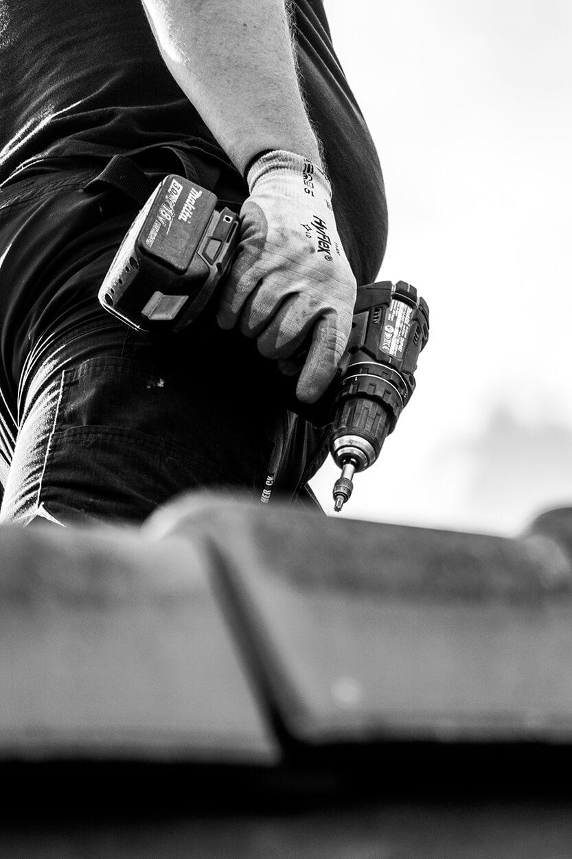 Close-up van een hand dat een boormachine vast heeft (zwart-wit).