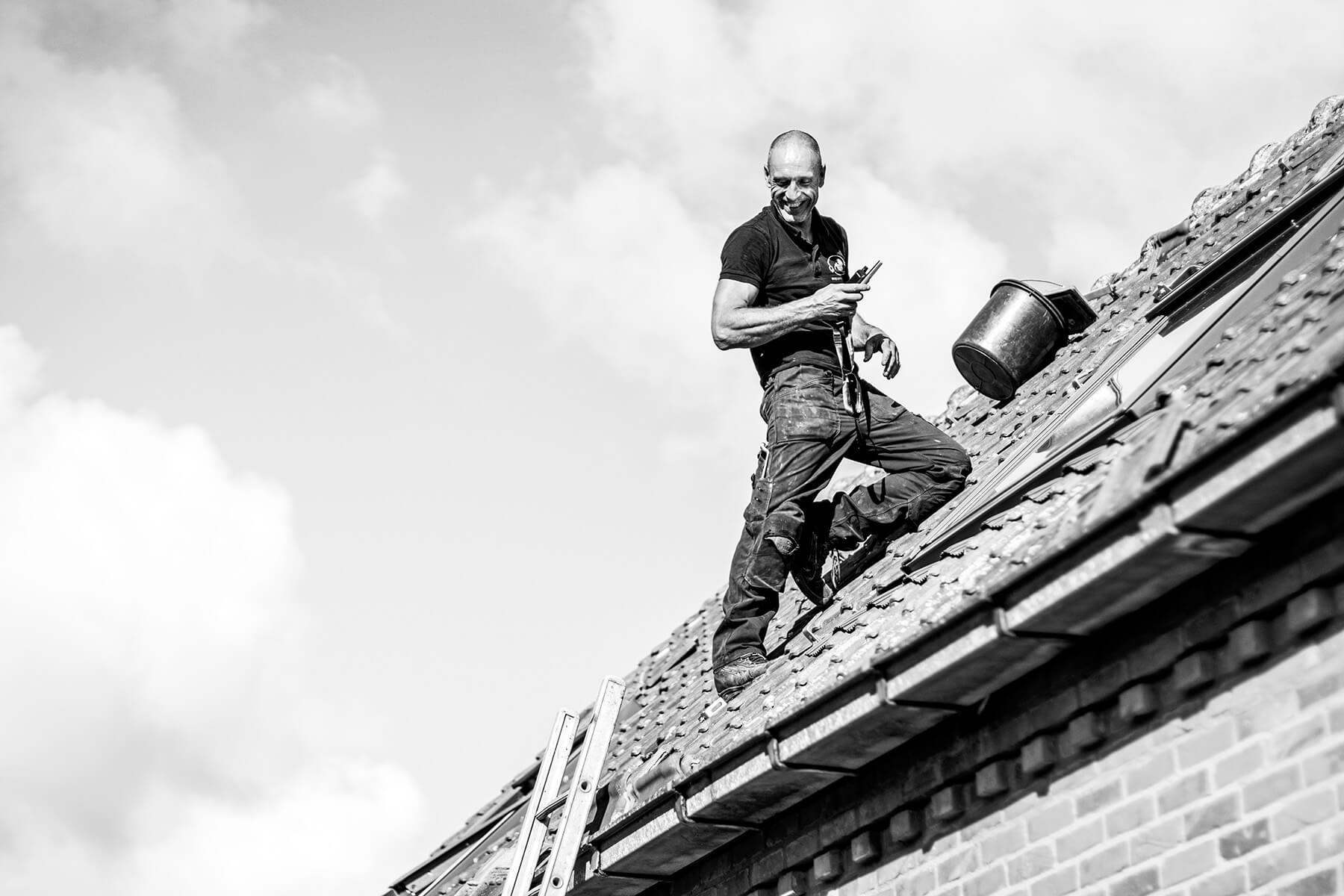 Werknemer van de Wase Groene Stroom al lachend aan het werk op een dak.