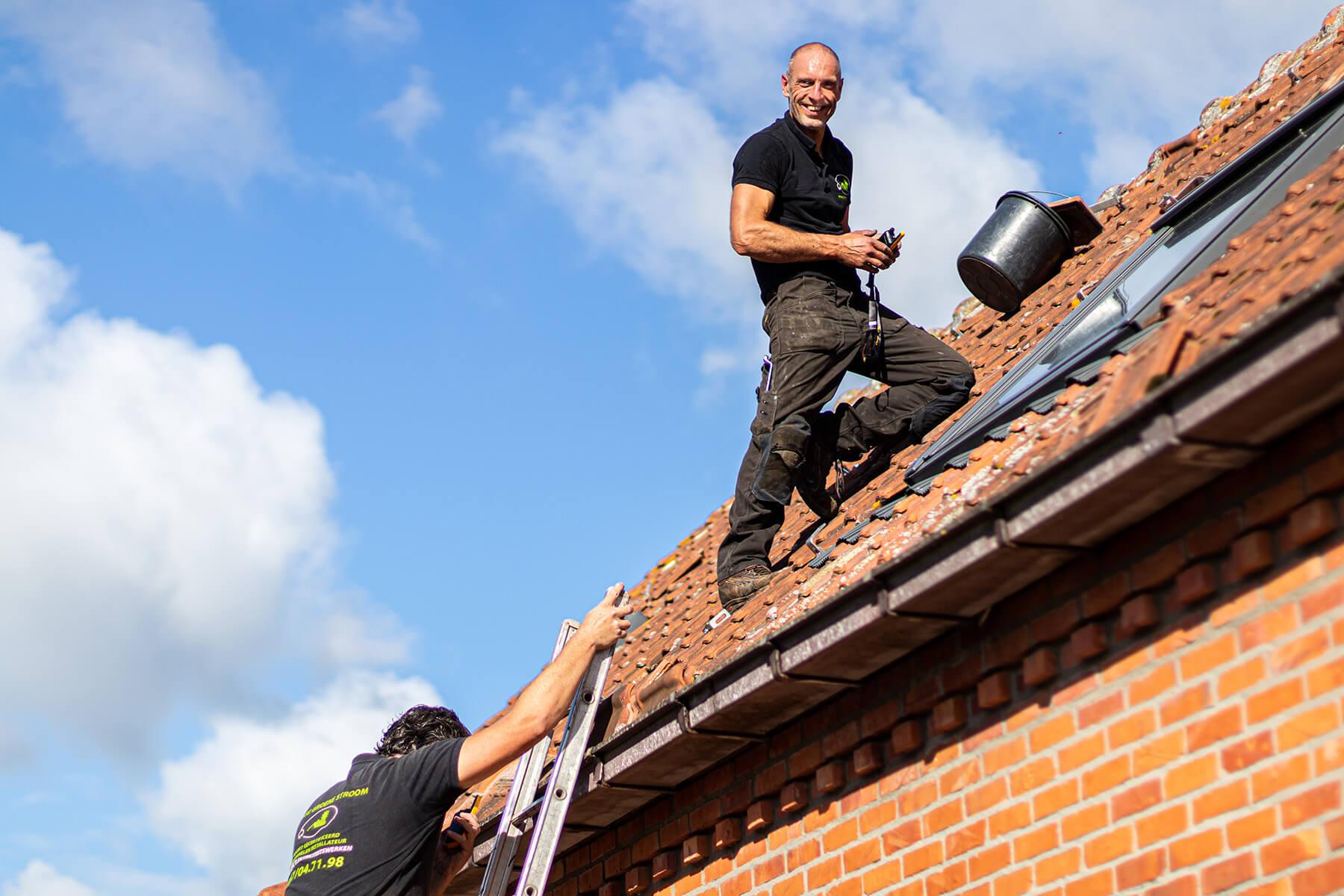 Zonnepanelen installateur op een steil dak die een meting uitvoert bij helderblauwe hemel met enkele wolken in het waasland.