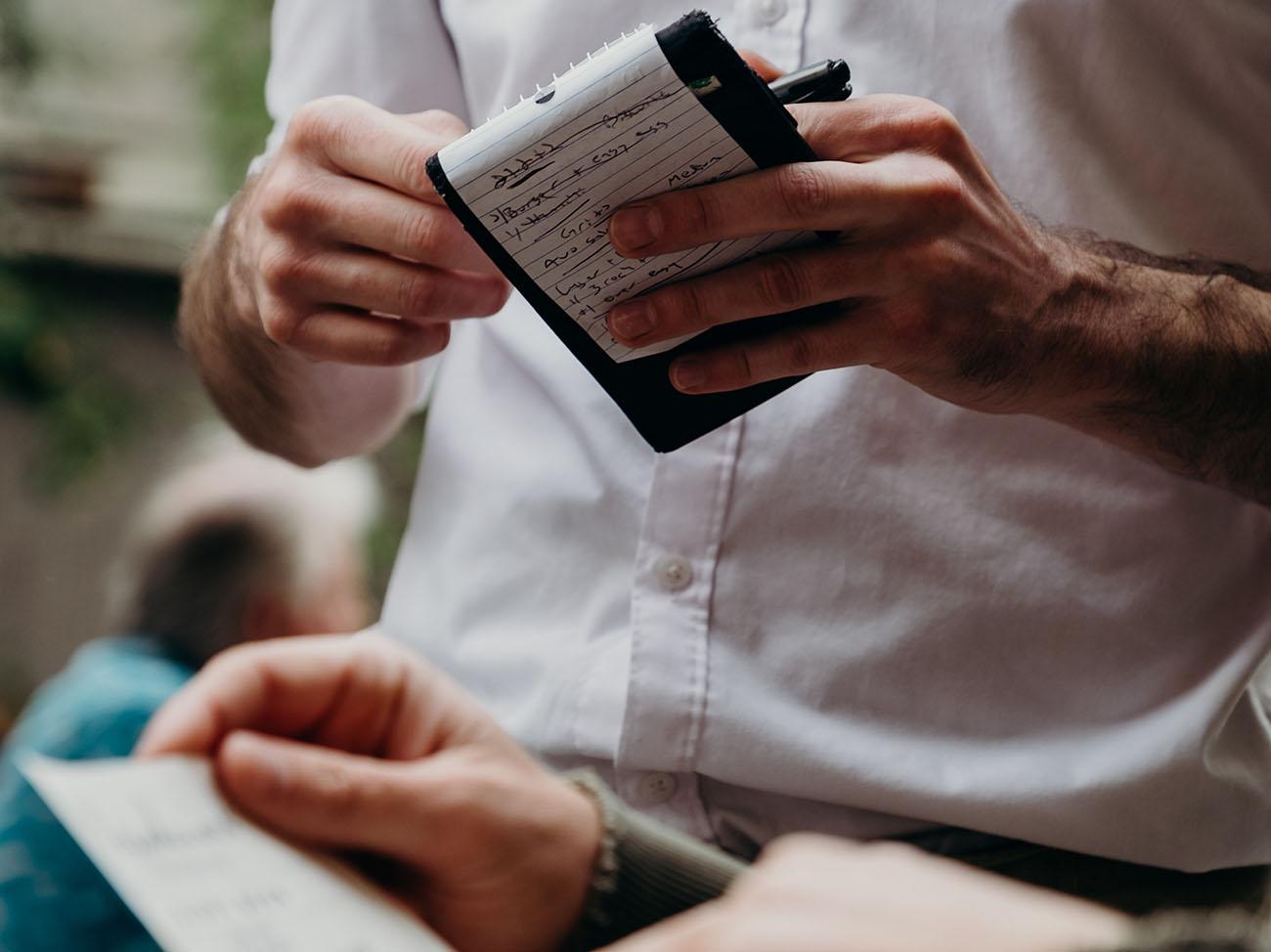 Mann mit Notizblock und Frau mit Dokumenten