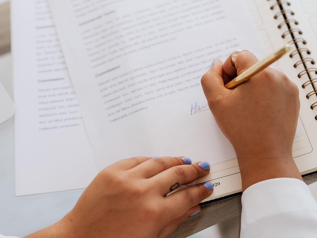 Frau unterschreibt wichtige Dokumente