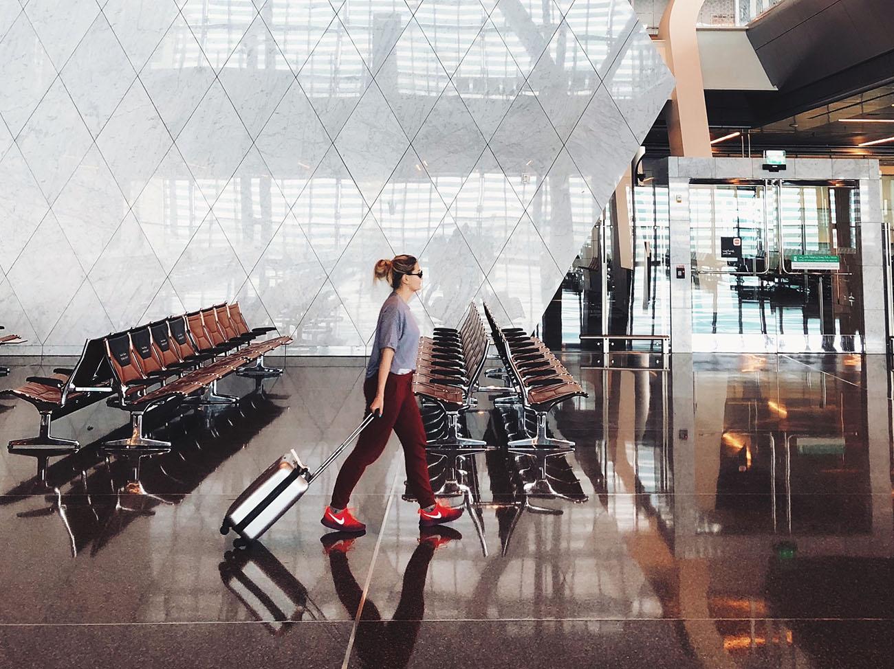 Frau läuft mit Koffer und roten Schuhen in Flughafen