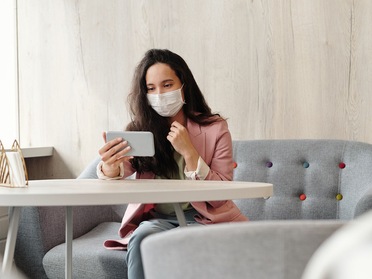 Geschaeftsfrau sitzend mit medizinischer Mask