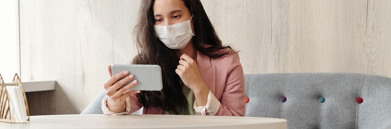 Frau mit Gesichtsmaske schaut auf Smartphone