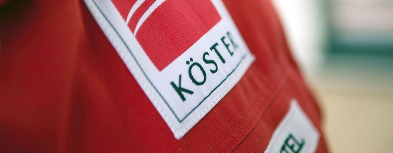 Roter Overall mit Koester-Logo