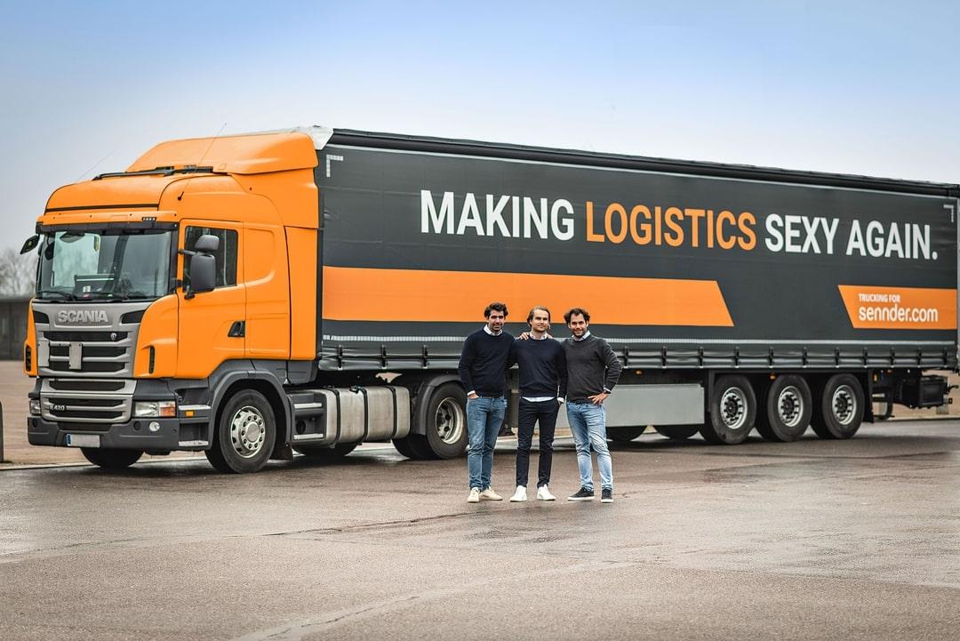 Oranger sennder-LKW mit Gründerteam