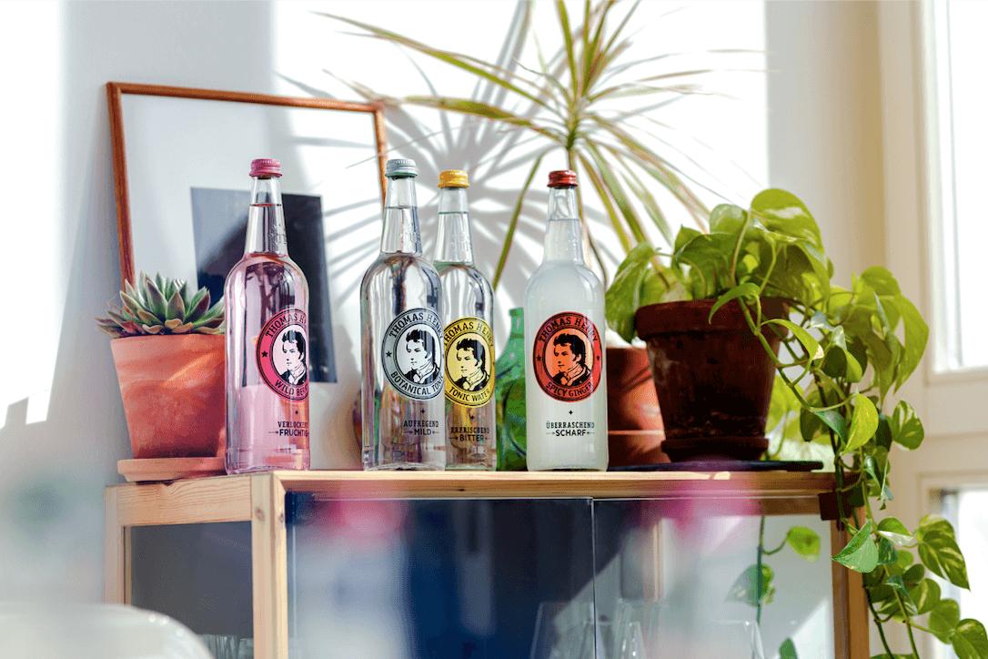 Foto von vier großen Thomas Henry Flaschen auf einer Bar mit Pflanzen und Bilderrahmen