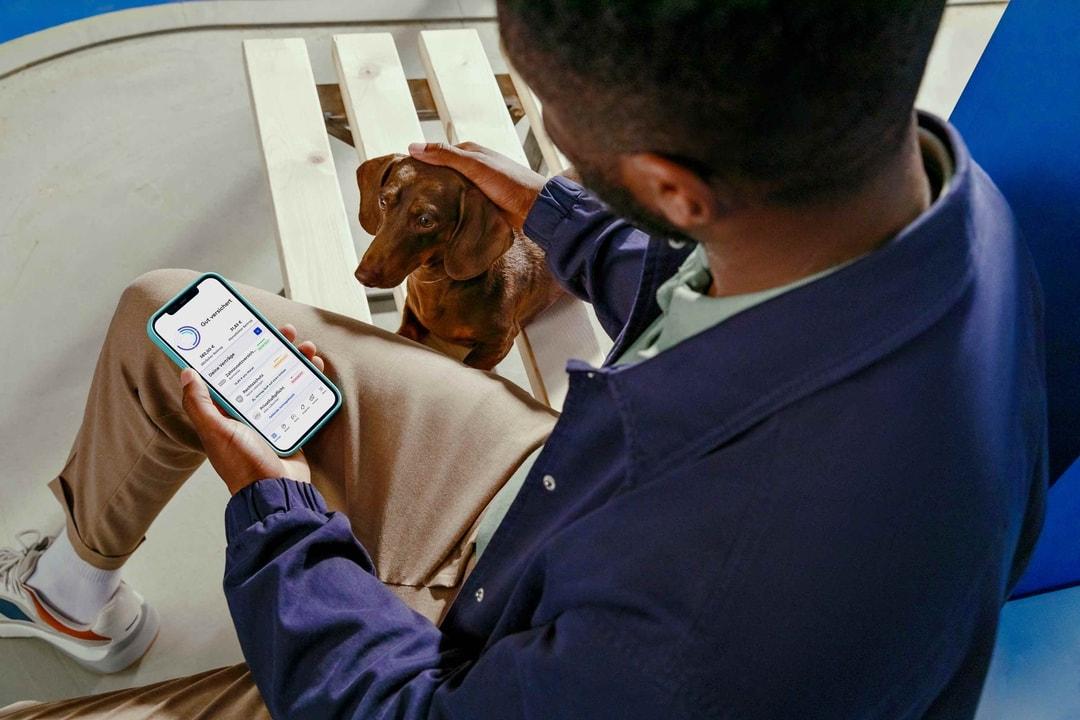 Foto von Mann mit geöffneter CLARK-App und Dackel