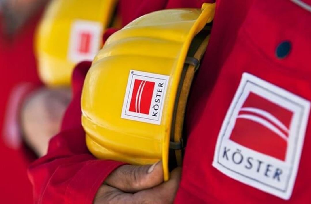 Zwei Koester Bauarbeiter in rotem Overall mit gelbem Helm