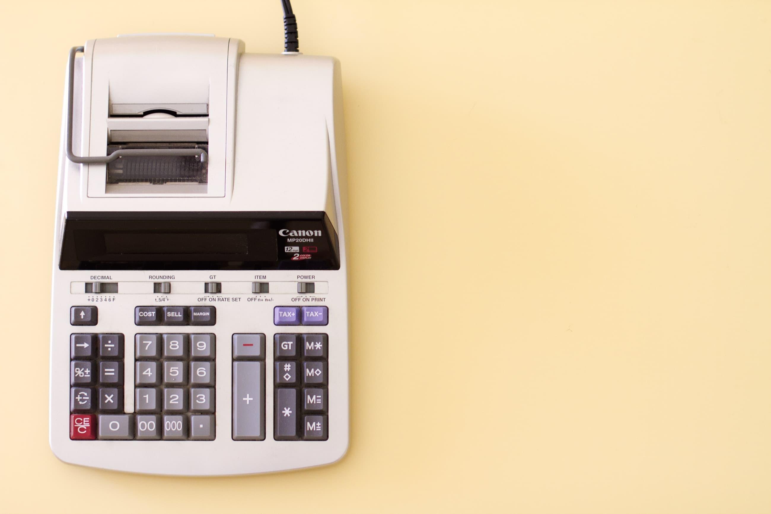 Foto von Tischrechner mit Papierrolle auf hellgelbem Hintergrund
