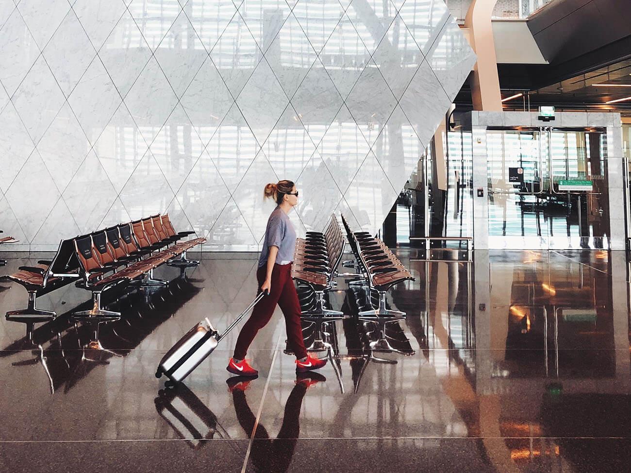 Frau läuft mit Rollkoffer und roten Schuhen in Flughafen