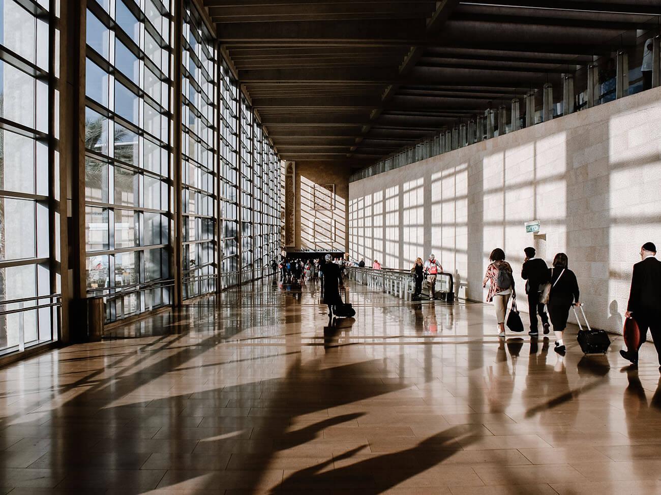 Personen laufen in Flughafenhalle in verschiedene Richtungen
