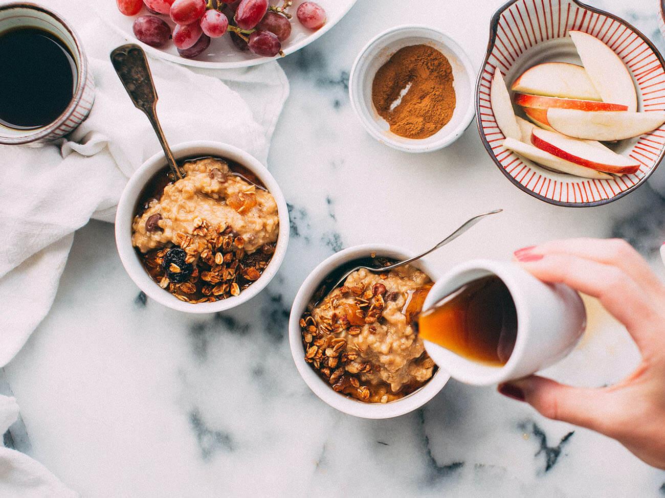 Frau gießt Sirup zum Porridge zum Fruestueck