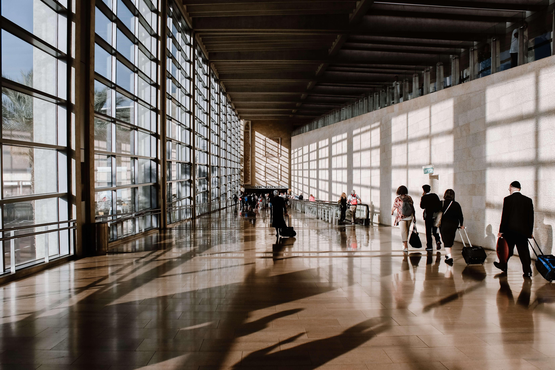 Foto von lichtdurchflutetem Flughafen mit Reisenden auf Rollband