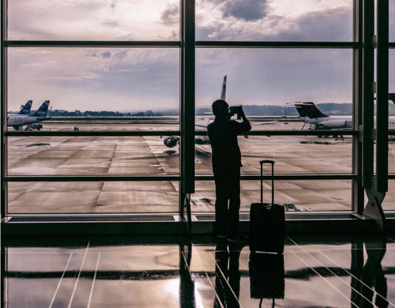 Reisender im Gegenlicht fotografiert Flugzeug am Flughafen