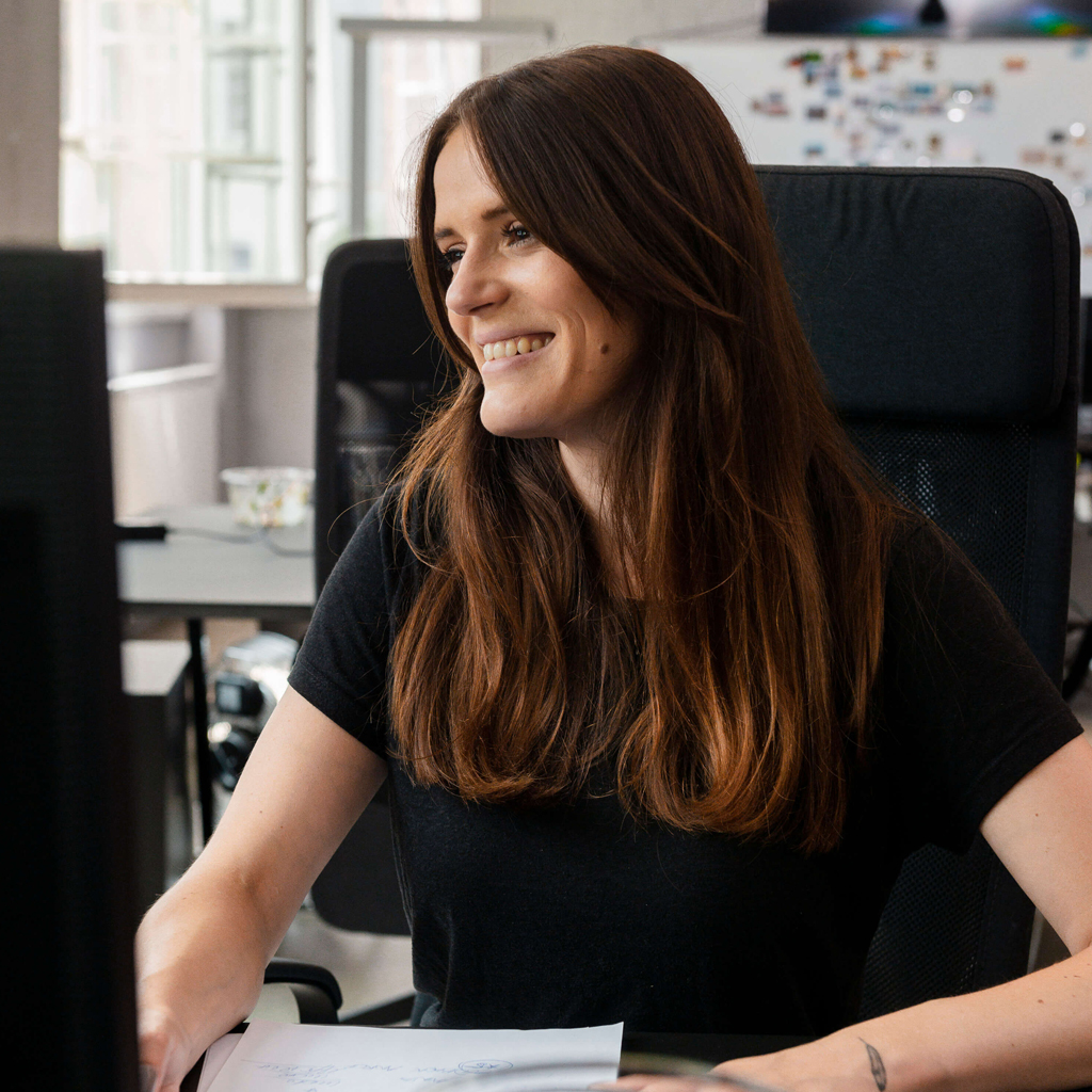 A smiling woman sitting at her desk at work