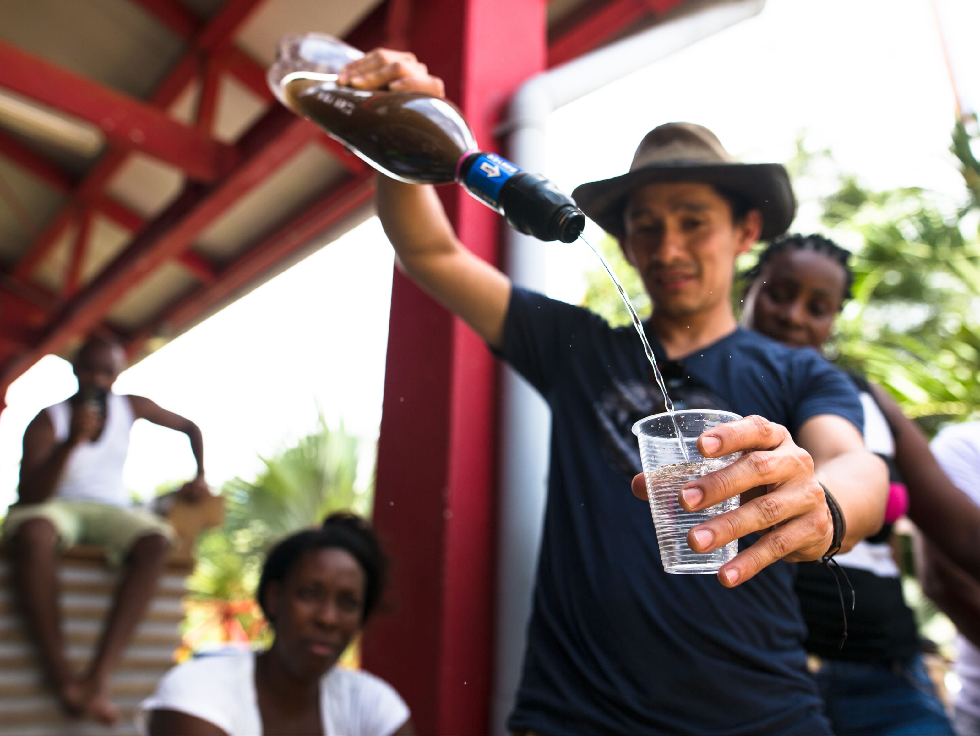 A Sawyer volunteer pours water from a Sawyer filter into a cup. The water in the filter is murky and what comes out is clear.