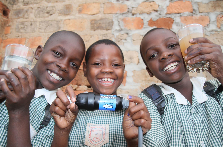 Three children use a Sawyer filter as part of an international project.