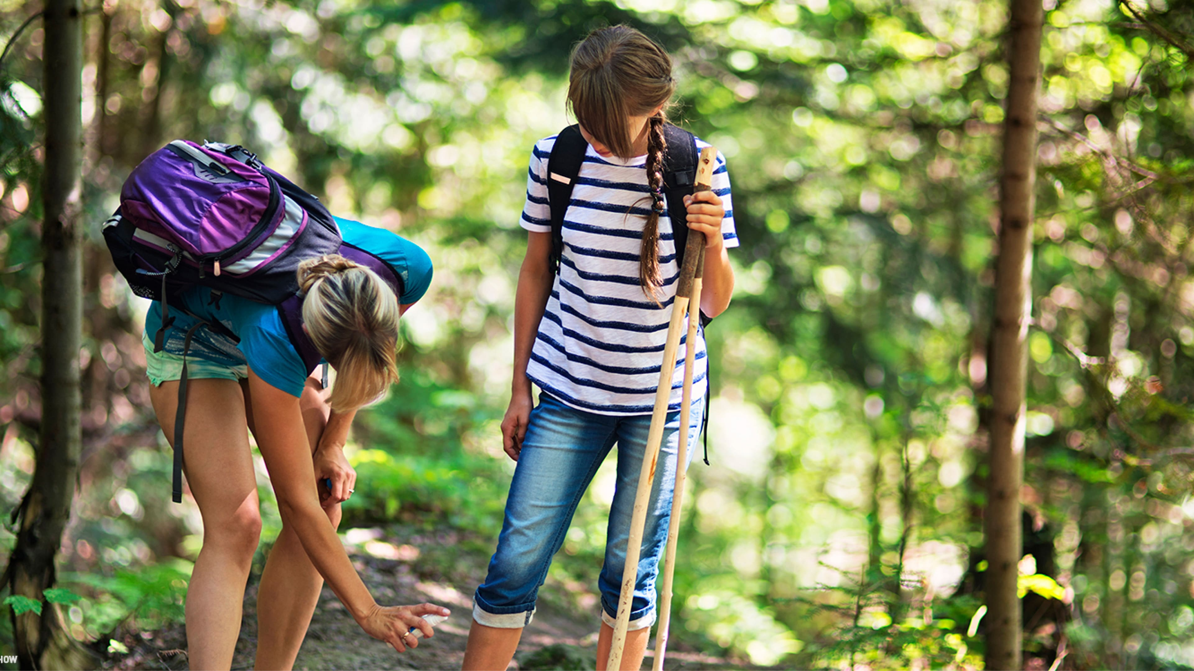 A woman applied insect repellent to her daughter as they prepare to hike through the woods.