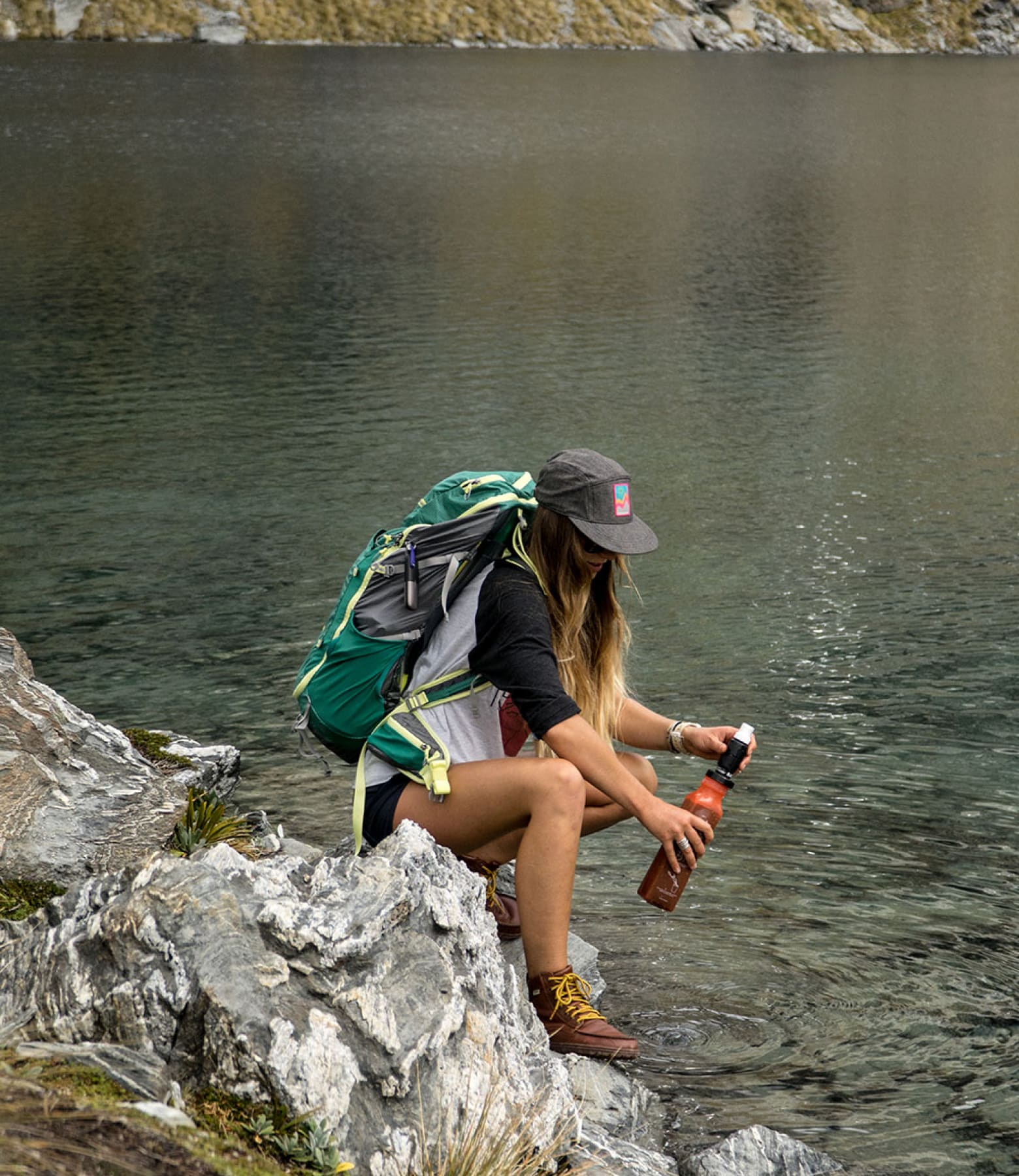 A woman fills her Sawyer filter from a river.