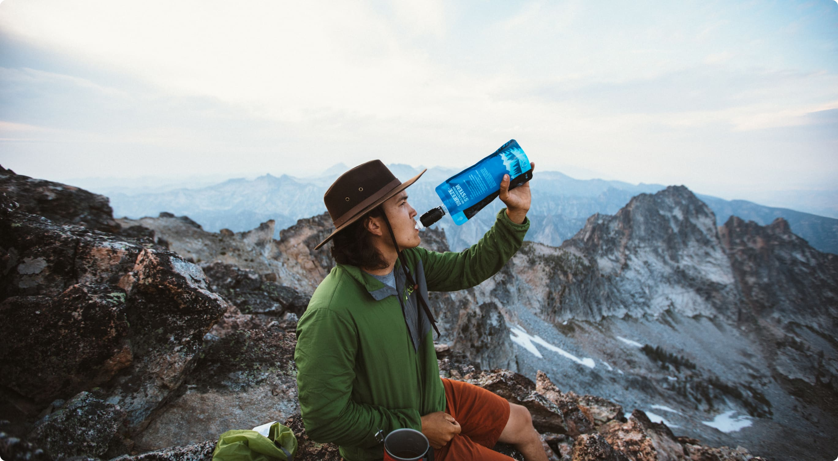 A man drinks from a Sawyer water filter while taking in a panoramic view of mountains.