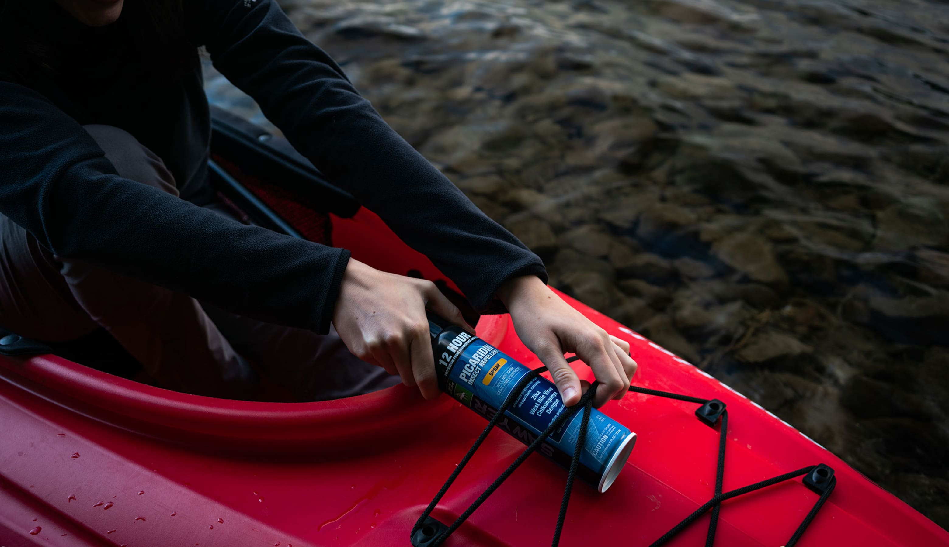 A canoeist ties Sawyer Insect Repellent into a canoe.