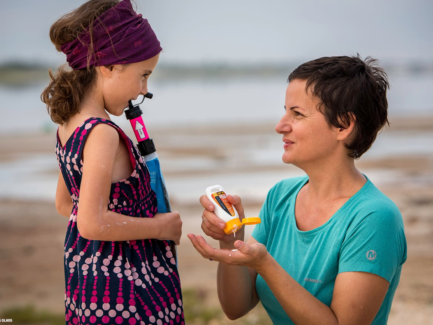 A woman applies sunscreen to her daughter, who is drinking out of a Sawyer water filter.