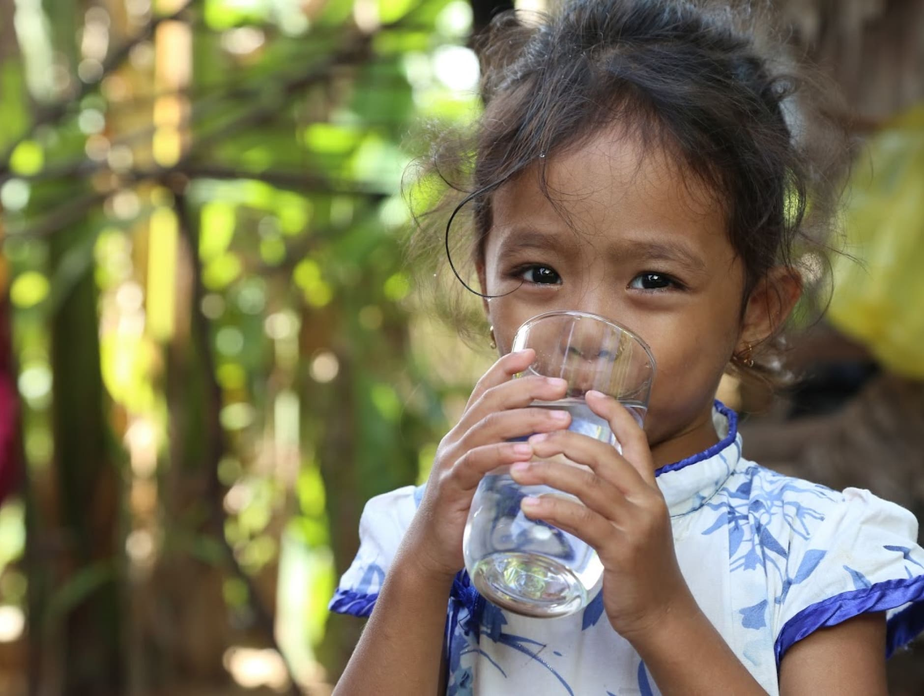 A little girl drinks clear water from a glass.