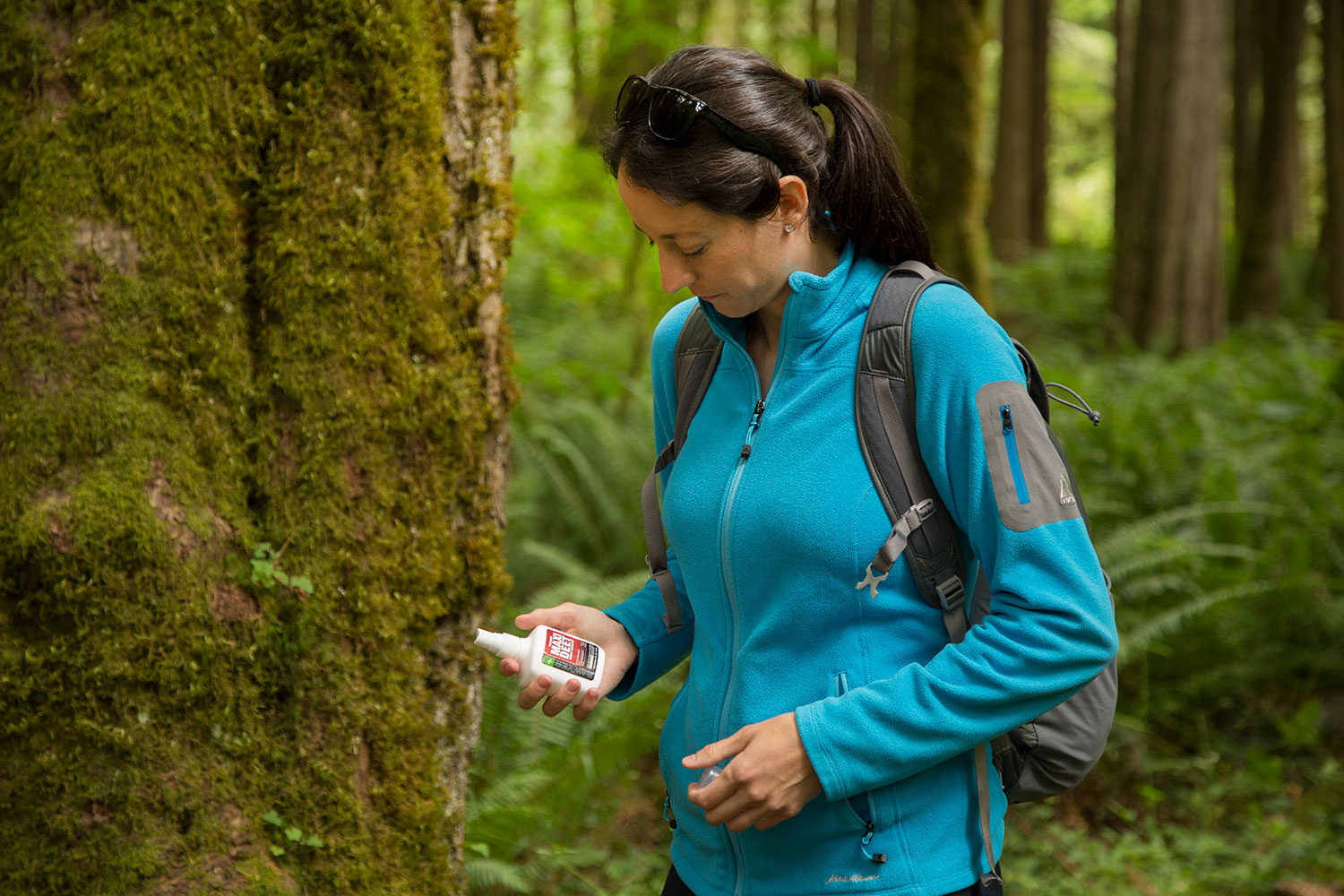 A Woman Read the Label of her Sawyer MAXI DEET Insect Repellent Spray while Hilking