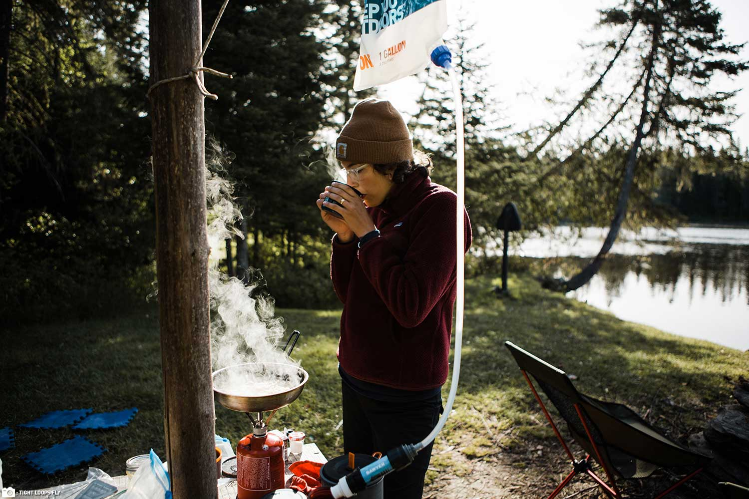 A Sawyer Gravity Filtration System Hanging at Fishing Camp While a Woman Sips Coffee