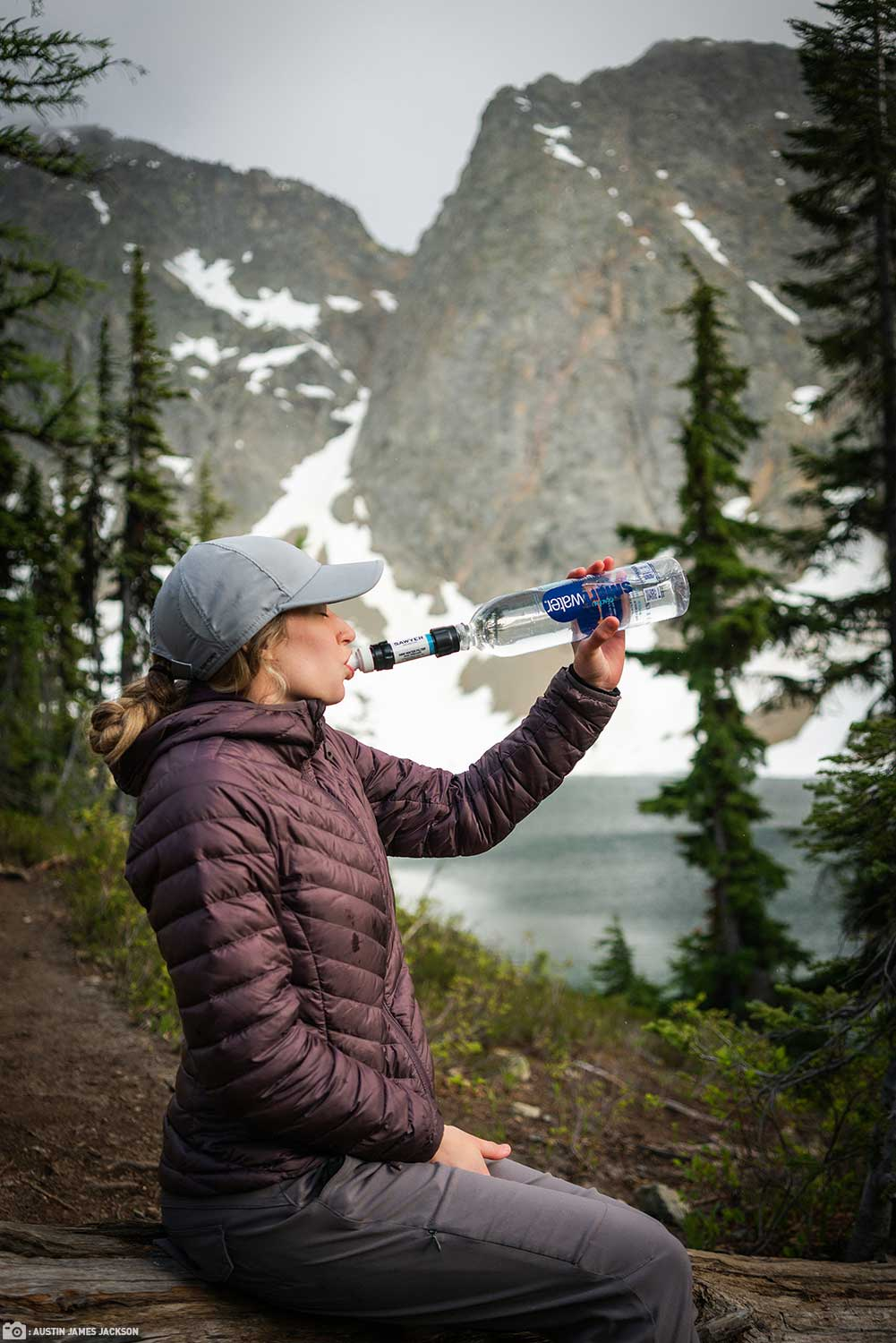 A Woman Drinking Freshly Filtered Water from her Sawyer Dual Threaded MINI Filter on a Smartwater Bottle