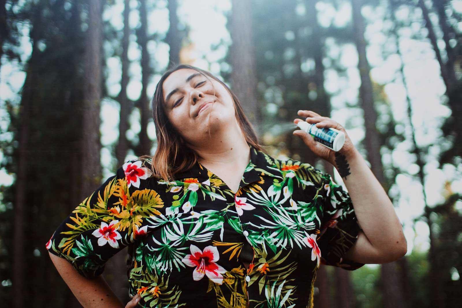 A Hiker Wearing a Hawaiian Shirt Sprays Herself with Sawyer Picaridin Insect Repellent