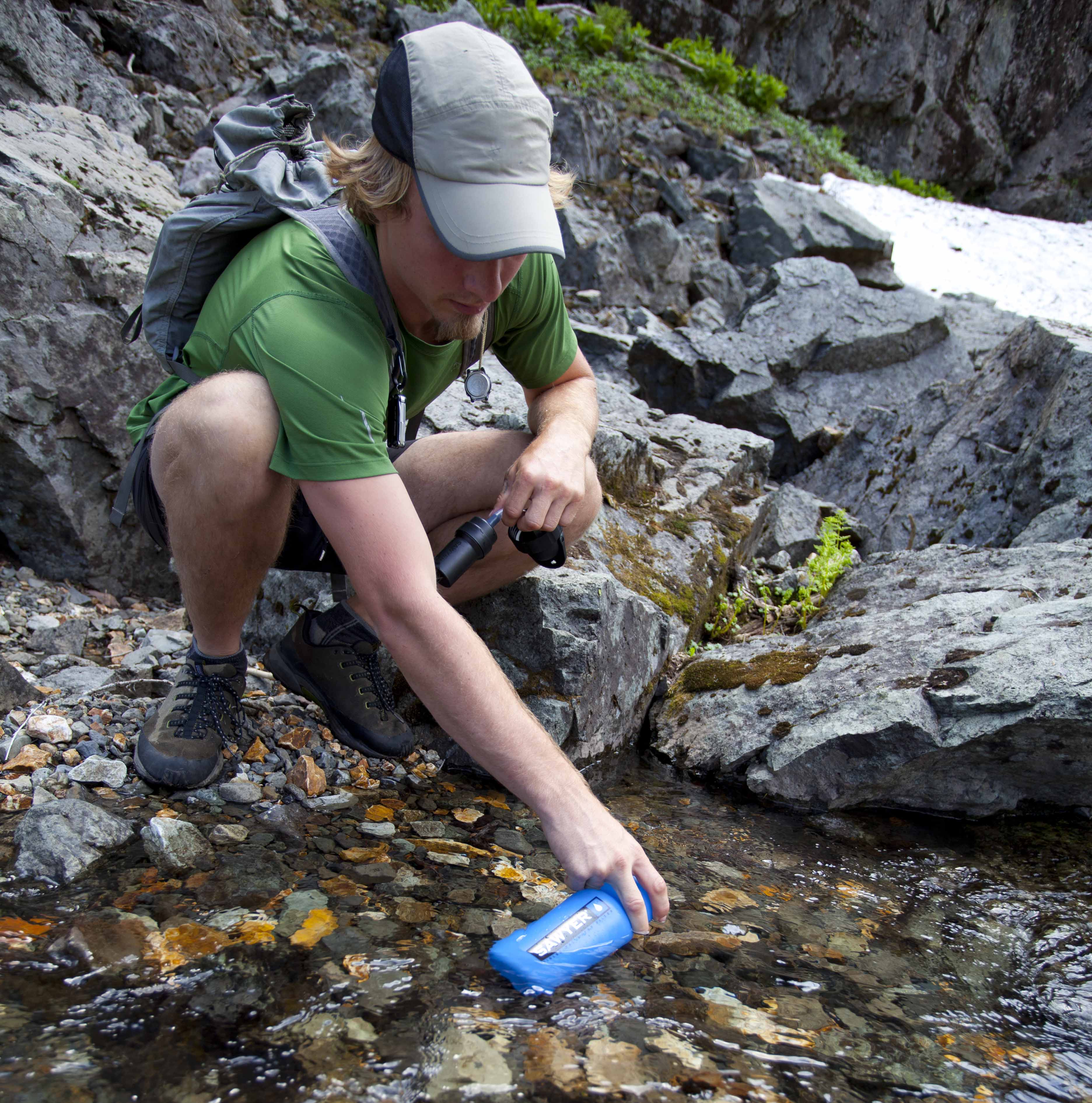 Gentleman Filling his Sawyer Personal Water Filtration Bottle in a Stream