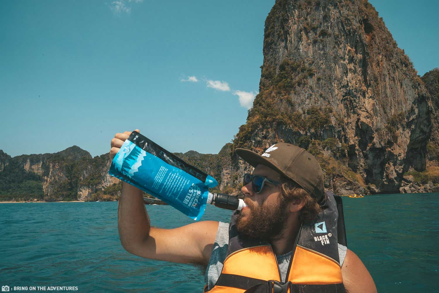 A Gentleman Drinking Water From His Sawyer Micro Squeeze Water Filter While Kayaking
