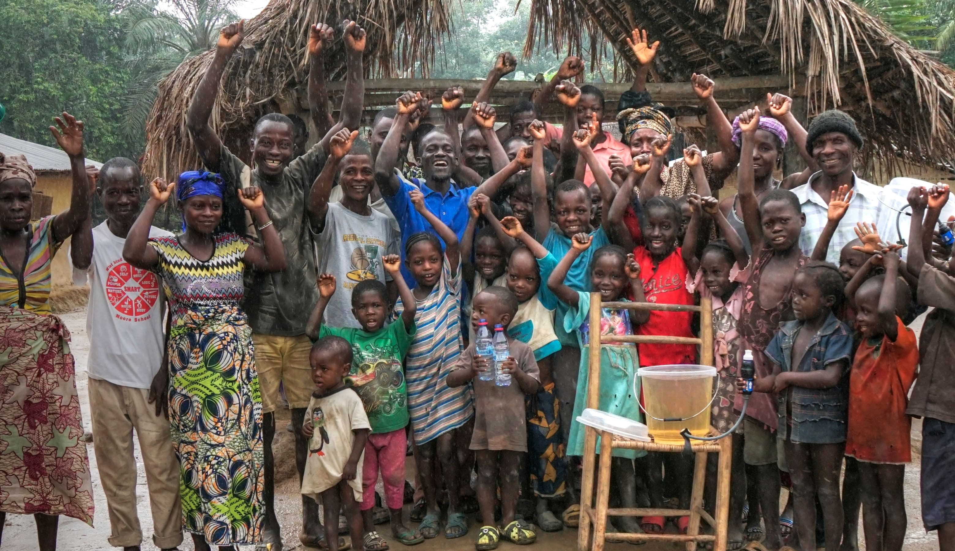 A group of Liberians poses for a photo with a Sawyer tap kit positioned in front of them.