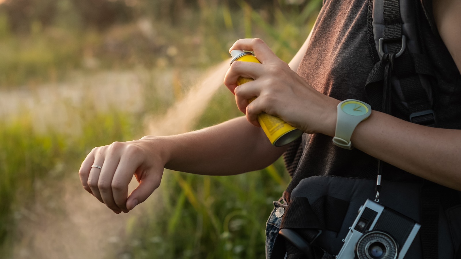 Woman using anti mosquito spray outdoors at hiking trip.