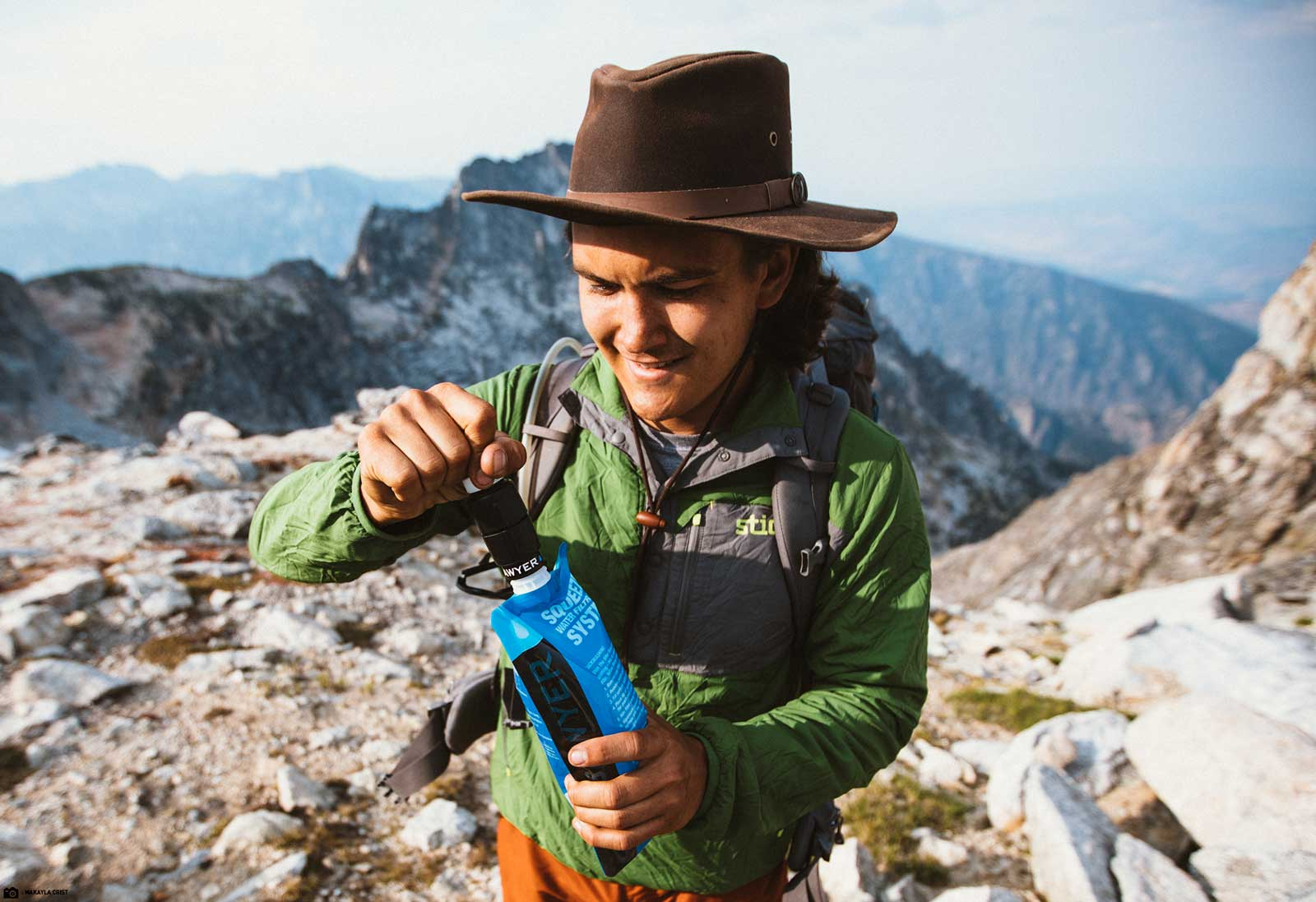 A Gentleman Prepares to Drink Water from his Sawyer Micro Squeeze Water Filter on top of a Mountain